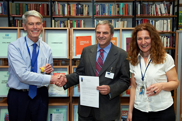 Mr Ted Whiteside, NATO Deputy Assistant Secretary General, shakes hands with Mr Giuseppe Vitiello, Head, NDC Library and Knowledge Centre. On the right, Mrs Isabel Fernandez, Head, NATO Multimedia Library