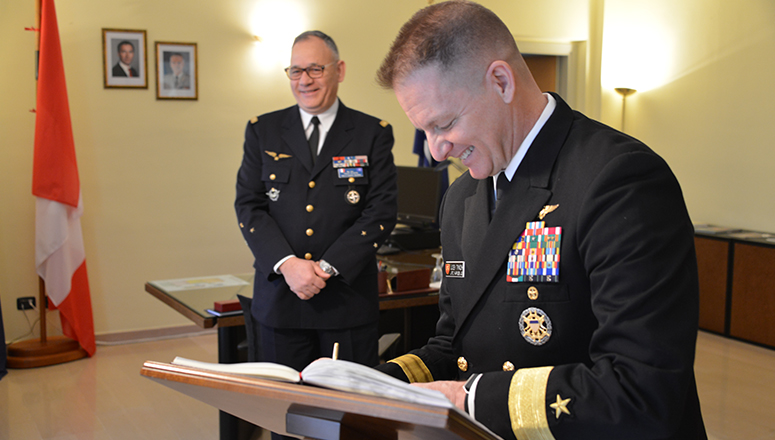 Rear Admiral Tynch signs the NDC guest book.